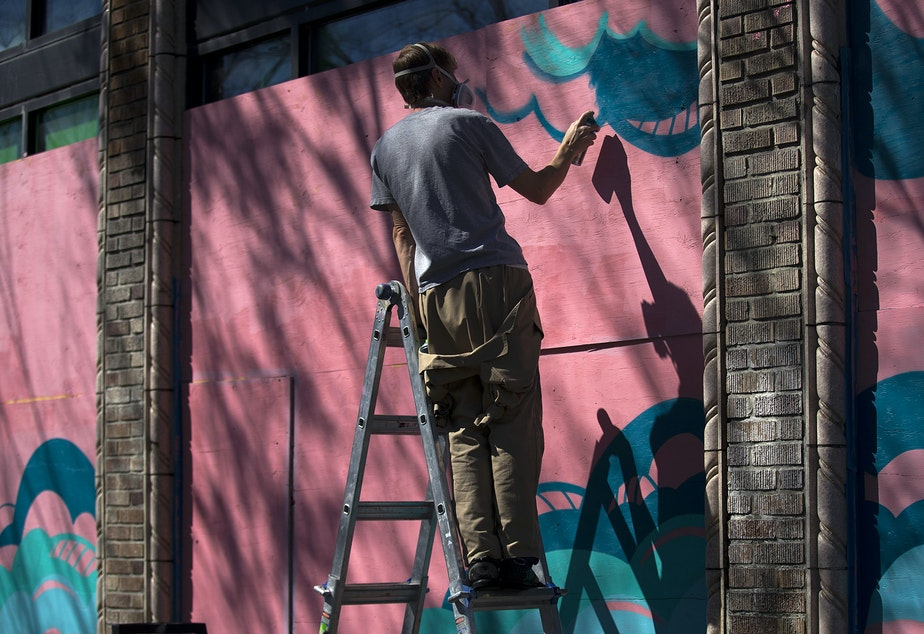 "caption: Artist Sam Trout paints a mural on Monday, April 20, 2020, at the intersection of Broadway East and East Harrison Street in Seattle. When complete, the mural will show two astronauts  with the words, ""I'll see you when we land."""