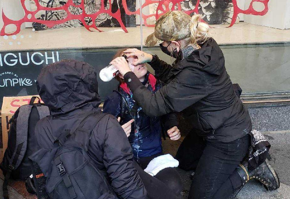 caption: A bystander washes pepper spray from the face of a protester outside the Macy's in downtown Seattle on Saturday, May 30, 2020. Thousands of people were protesting the death in Minneapolis of George Floyd at the hands of police.