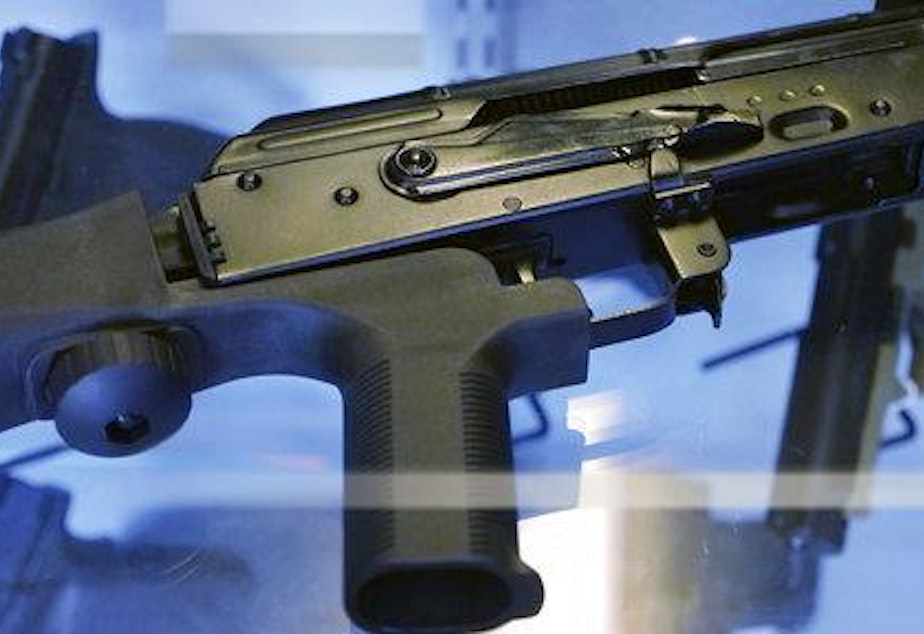 """caption: In this Oct. 4, 2017, photo, a device called a """"bump stock"""" is attached to a semi-automatic rifle at the Gun Vault store and shooting range in South Jordan, Utah. 18355688918754"""