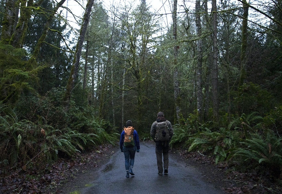 Forest therapy guide and educator Julie Hepp, left, and Chris Morgan walk through the woods on Friday, January 18, 2019, at IslandWood, a learning center on Bainbridge Island.