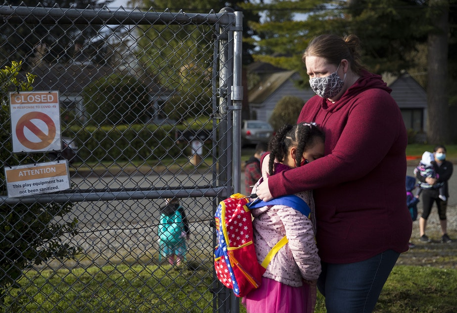 caption: Alayna Holmes, a first-grade student at Northgate Elementary School, hugs her mom, Michelle Holmes, while saying goodbye on Monday, April 5, 2021, on the first day of in-person learning at the school in Seattle.