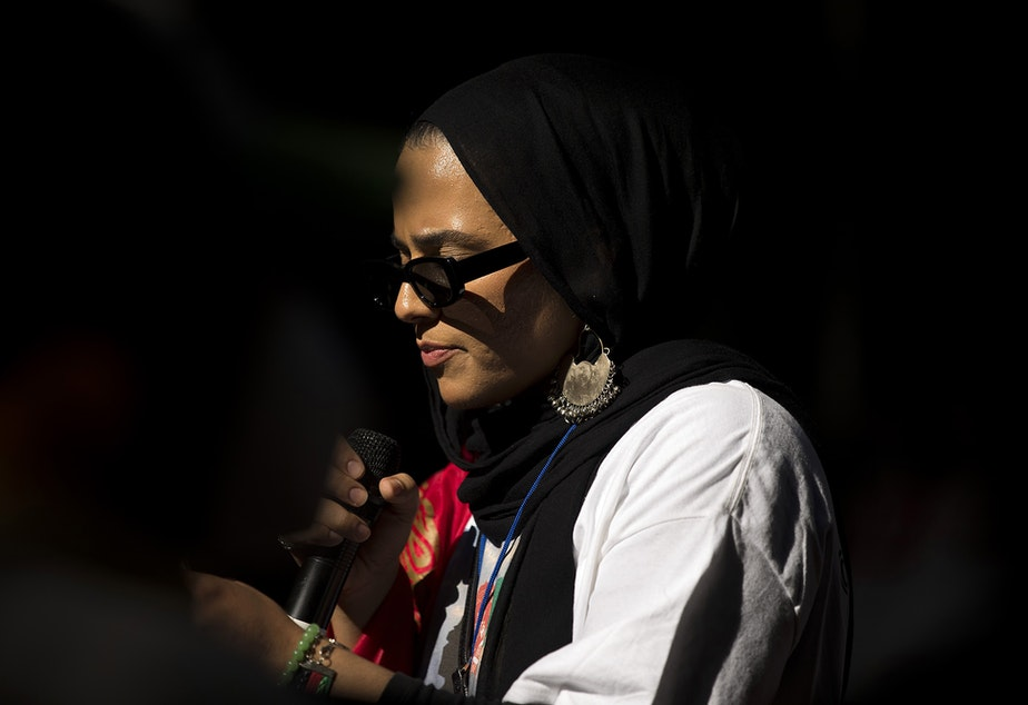 """caption: Shugla Kakar, a founding member of Afghans of Seattle, leads a march of about 100 people standing in solidarity with Afghans on Saturday, August 28, 2021, near Westlake Park in Seattle. """"What is happening in Afghanistan is devastating,"""" said Kakar. """"We're trying to amplify Afghan voices and experiences, and push for urgent action by our federal, state and local leaders to help evacuate those at grave risk in Afghanistan while also supporting the incoming Afghan refugees in our state."""""""