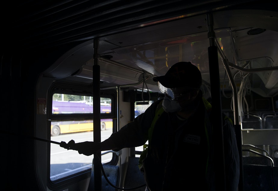 caption: Larry Bowles, an equipment service worker with King County Metro, sprays a Virex II cleaning solution on the interior of a King County metro bus on Wednesday, March 4, 2020, at the Atlantic Base on 6th Avenue South in Seattle.