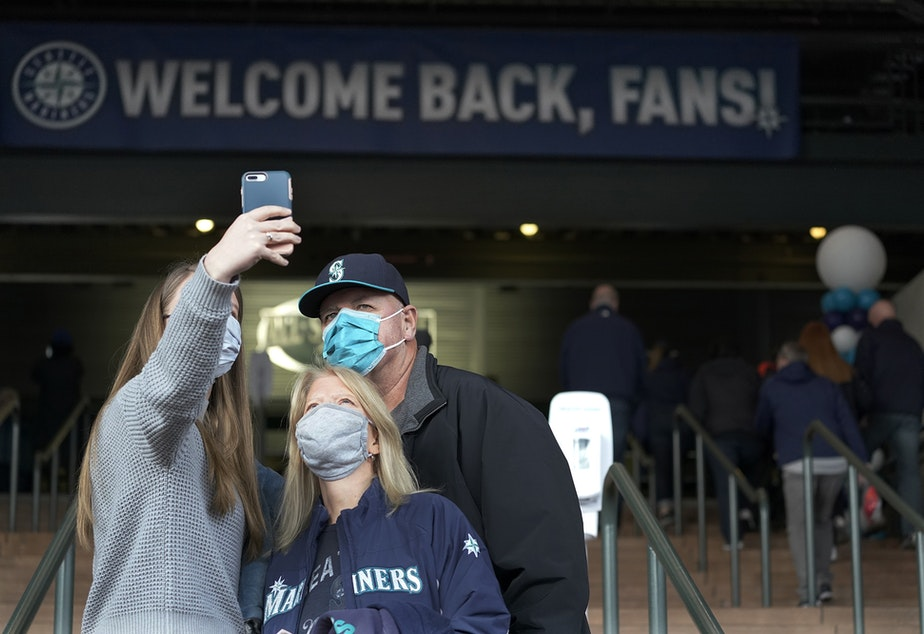 caption: A group of fans takes a selfie after entering T-Mobile Park for the Seattle Mariners opening-day baseball game against the San Francisco Giants, Thursday, April 1, 2021, in Seattle.