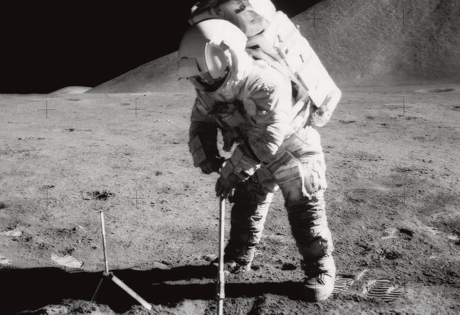 caption: Astronaut James B. Irwin, lunar module pilot, uses a scoop in making a trench in the lunar soil during Apollo 15 extravehicular activity (EVA). Irwin had a heart attack while orbiting the moon, which made NASA realize that they needed a better health monitoring system.
