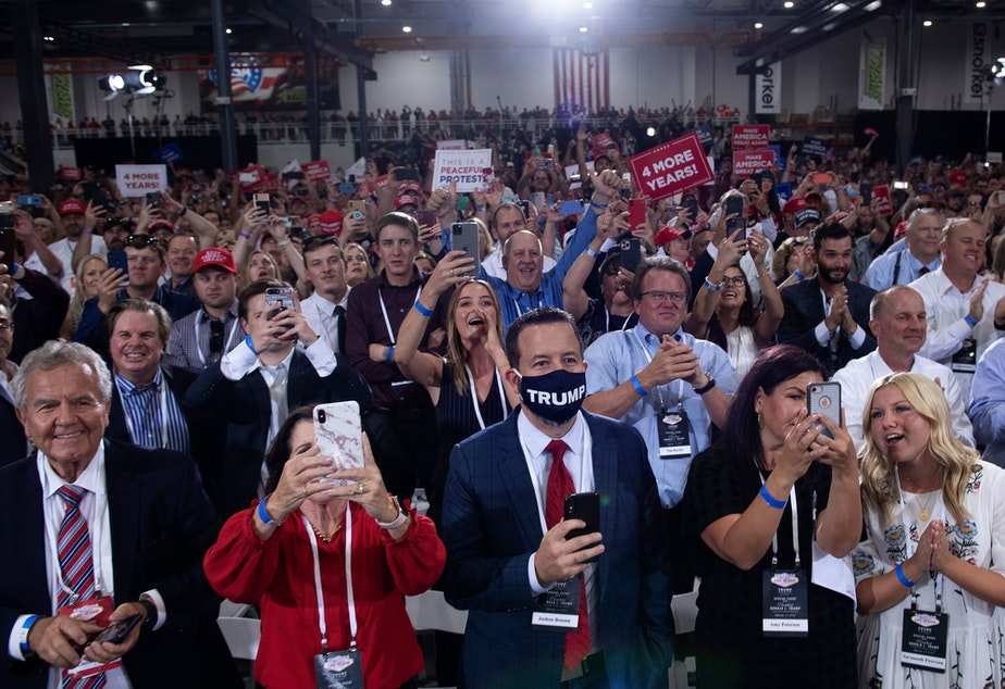 caption: People cheer as President Trump arrives for an indoor campaign rally Sunday night at Xtreme Manufacturing in Henderson, Nev.