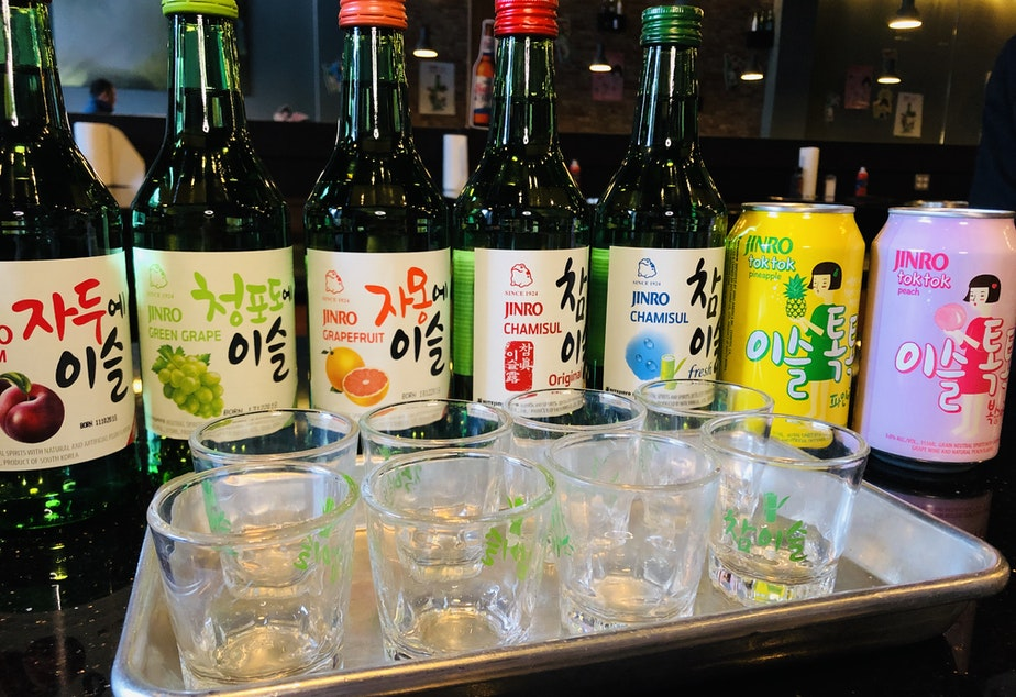 caption: State liquor laws require restaurants to serve distilled spirits like soju by the shot glass. In Korean tradition, it's served by the bottle.