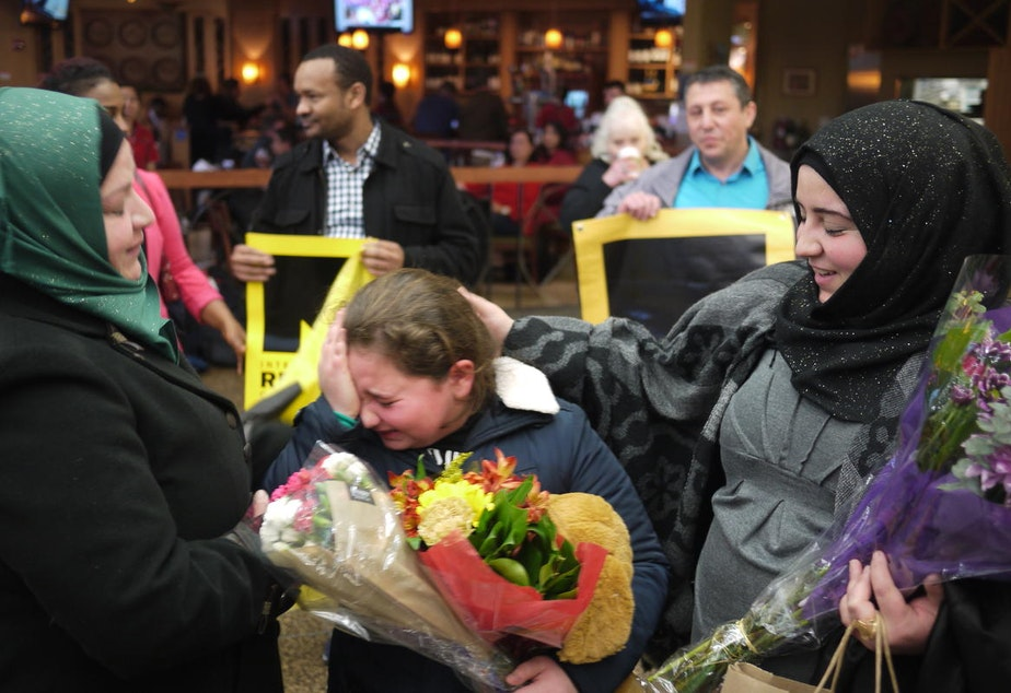 caption: Syrian refugee Alaa Al Halabi, 11, is overcome with emotion as her siblings arrive in Seattle on Februray 9, 2017. The siblings were delayed by the Trump Administration's initial travel ban.
