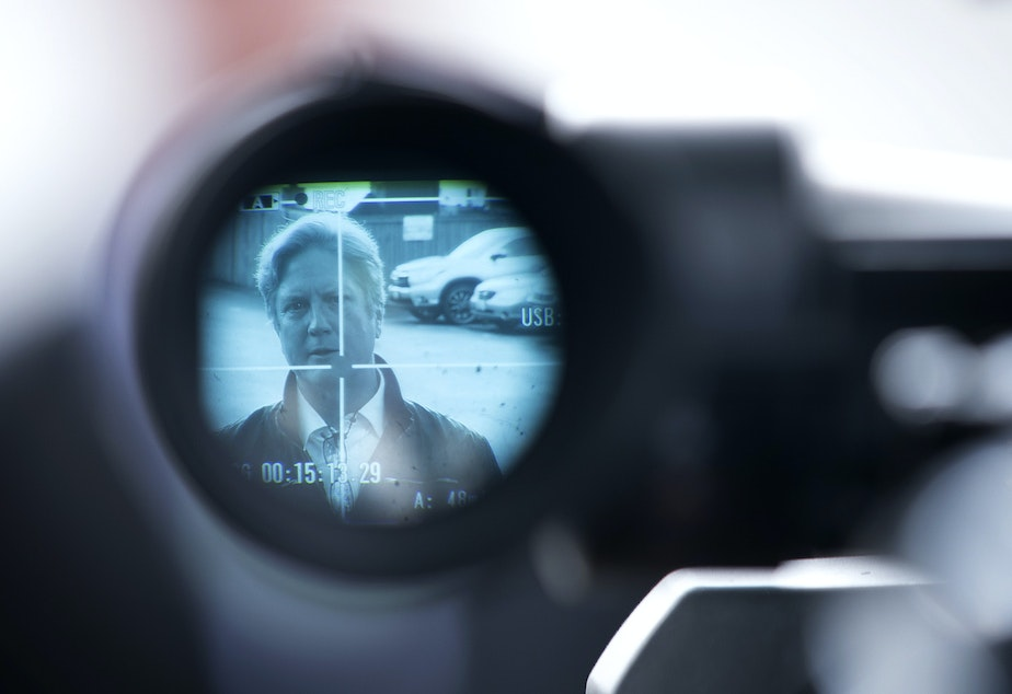 caption: Tim Killian, a public liaison for the Life Care Center of Kirkland, is shown through the viewfinder of a video camera while speaking to the press outside of the long-term care facility on Sunday, March 8, 2020, in Kirkland.