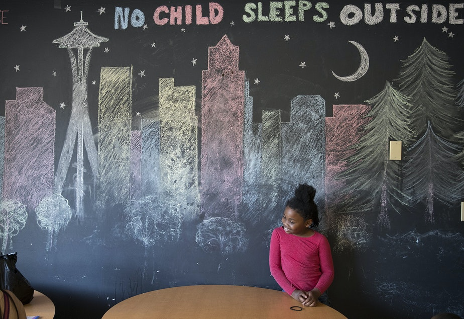 caption: Mariah Hicks, 7, stands in front of a chalk drawing depicting downtown Seattle in a common area at Mary's Place, a homeless shelter.