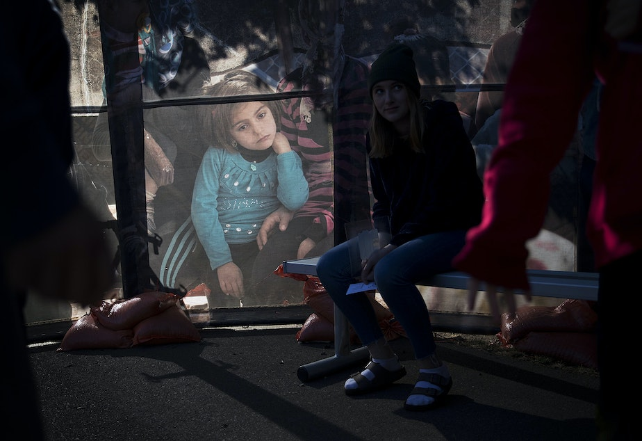 Light shines through a poster with a photograph of a displaced child as students from Morningside Academy gather around the Forced From Home exhibit on Tuesday, October 3, 2017, at the South Lake Union Discovery Center in Seattle.