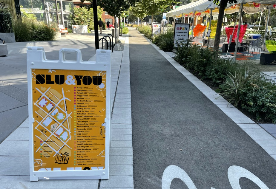 caption: SLU & You, part of Amazon's marketing campaign to draw attention to businesses on its campus. Visible at right, outdoor shelters created by Amazon in an attempt to liven up 6th Avenue