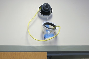 A camera with facial recognition capabilities hangs from a wall while being installed at Lockport High School in Lockport, N.Y.