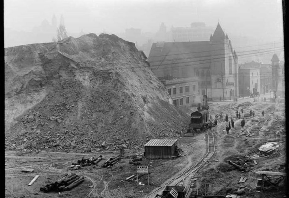 caption: The Denny Hill regrade in progress at 3rd Avenue and Pine, taken 1908 or 1909.