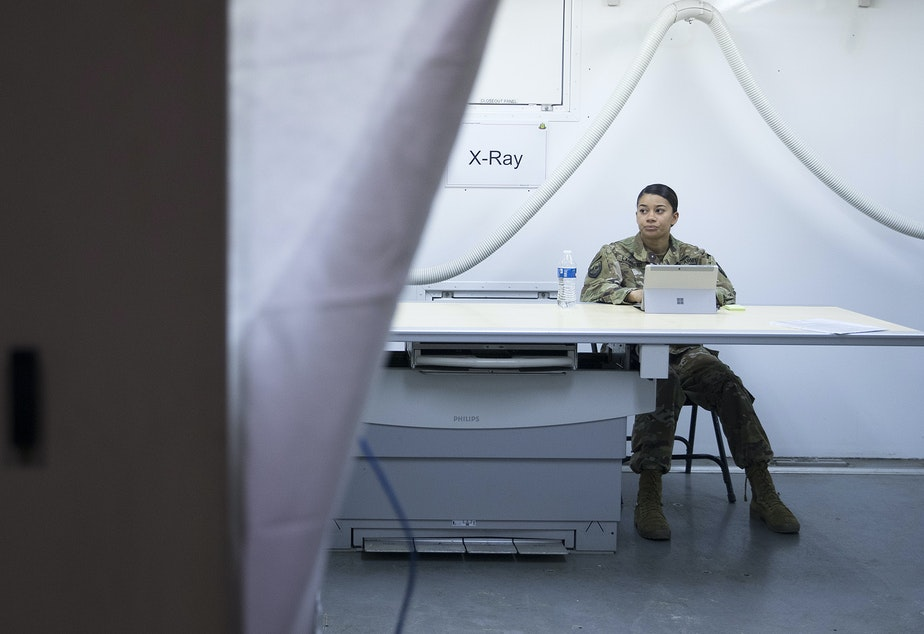 caption: Staff Sgt. Jordan Lambert sits inside the X-Ray area of the military field hospital inside CenturyLink Field Event Center on Sunday, April 5, 2020, in Seattle. The 250-bed hospital for non COVID-19 patients was deployed by U.S. Army soldiers from the 627th Army Hospital from Fort Carson, Colorado, as well as soldiers from Joint Base Lewis-McChord.