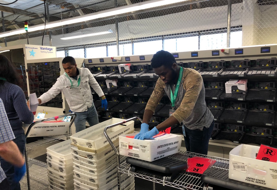 caption: Gloves are mandatory for King County elections staff like Dunia Wabenga, right.