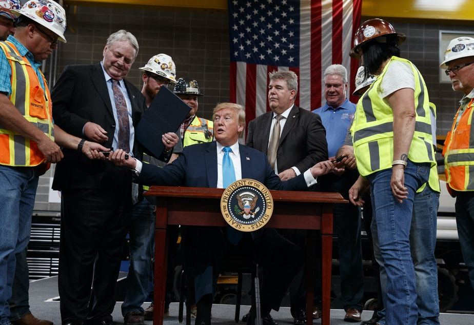 caption: President Trump hands out pens after signing an executive order aimed at making it easier for companies to pursue oil and gas pipeline projects. The president addressed an audience at the International Union of Operating Engineers International Training and Education Center in Texas.
