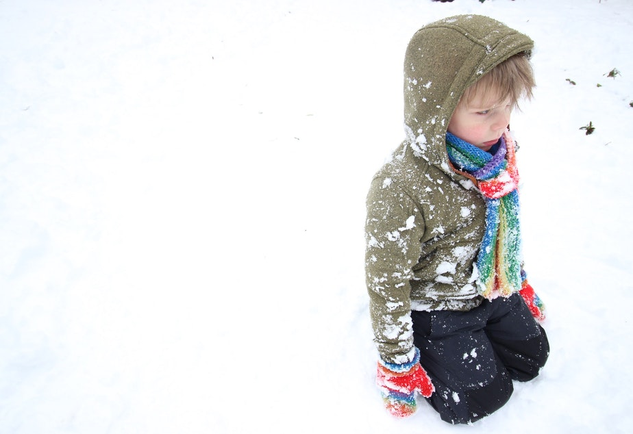 Oscar Pulkkinen, 5, sits in the snow after being pelted with snowballs.