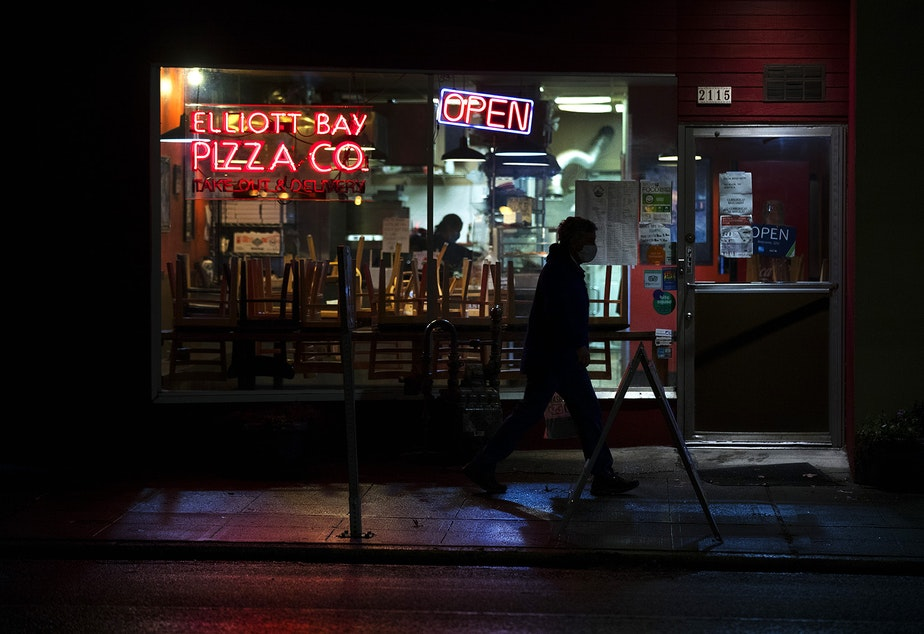 caption: A pedestrian walks in front of the Elliott Bay Pizza Co. & Flame Burger on Monday, November 16, 2020, along Queen Anne Avenue North in Seattle. New statewide restrictions, including a ban on indoor dining beginning Wednesday, were announced by Gov. Jay Inslee on Sunday to curb the rapid spread of Covid-19.