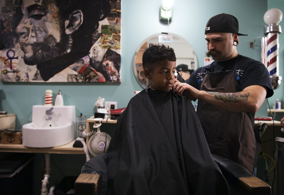 caption: Jayden Valencia, 6, has his hair cut by Chuck Hyte, right, at Uptown Barbershop on 4th St., on Thursday, June 8, 2017, in Bremerton, Washington.