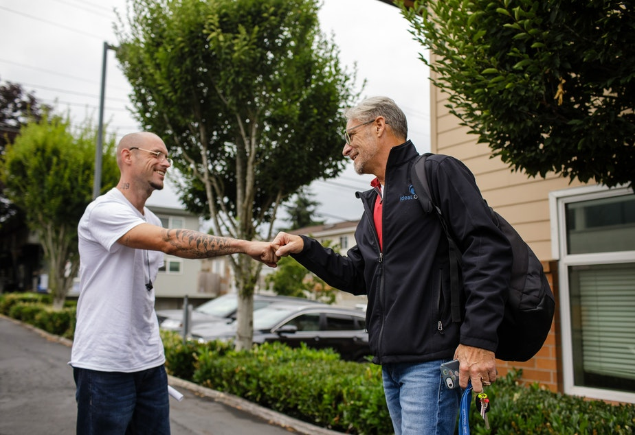 Geoff Godfrey (right) greets a patient outside the Ideal Option clinic in Everett, Wash. (Finding Fixes)