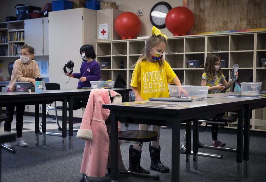 caption: Second grade student Camille, center, opens a container of school supplies that each student will keep in their cubby, while wearing a t-shirt that reads ' Somerset Strong No Matter the Distance,' in Ms. Gagne's classroom on Thursday, January 21, 2021, as second-grade students returned to in-person learning at Somerset Elementary School in Bellevue.