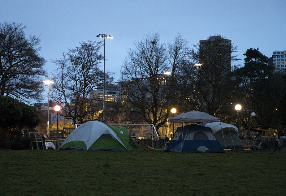 caption: Tents are shown near a barricade set up around the perimeter of an encampment where unhoused community members reside on Wednesday, December 16, 2020, ahead of a scheduled sweep by the Seattle Police Department at Cal Anderson Park in Seattle.