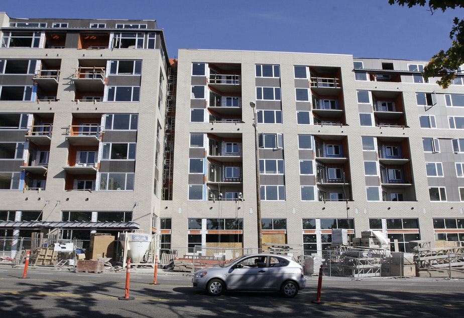 caption: In this Oct. 5, 2009, a driver goes past a large condominium under construction in the Ballard neighborhood of Seattle.
