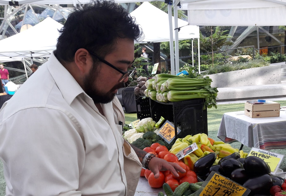 Chef Jay Guerrero checks out the vegetable stand at the Denny Regrade farmer's market.