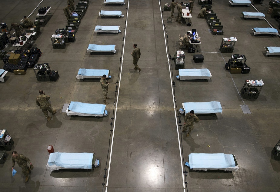 caption: U.S. Army soldiers from the 627th Army Hospital from Fort Carson, Colorado, as well as soldiers from Joint Base Lewis-McChord set up a 250-bed military field hospital for non COVID-19 patients on Tuesday, March 31, 2020, at the CenturyLink Field Event Center in Seattle.