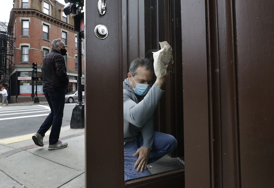caption: Manager Mike Bonavita wears a protective mask as he cleans windows at the Quattro Italian restaurant in Boston on May 12 during the coronavirus pandemic. This month, Massachusetts' governor declared wearing masks mandatory.