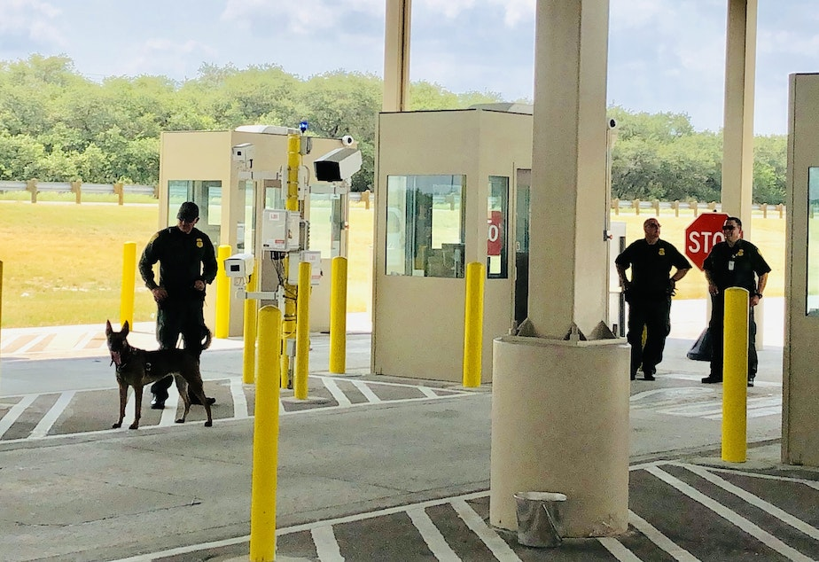caption: Border Patrol agents with a sniffer dog at the new and expanded Falfurrias checkpoint.