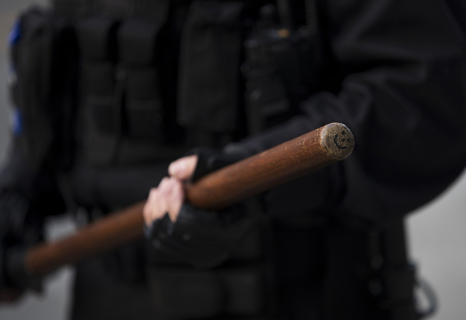 caption: A smiley face is shown drawn on the end of Seattle Police Officer M. Lancaster's baton while standing in a police line on Monday, June 1, 2020, at the intersection of 11th Avenue and East Pine Street in Seattle. For the next week, tense, nightly standoffs between demonstrators and a fortified line of police in riot gear took place at this intersection. On June 8, Seattle police abandoned the East Precinct.