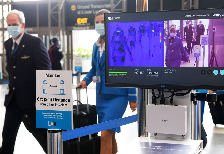 caption: Flight crew walk past thermal cameras that check passengers' body temperatures at Los Angeles International Airport on June 23. As businesses look to reopen, technology firms are offering an array of monitoring systems to try to control the coronavirus.