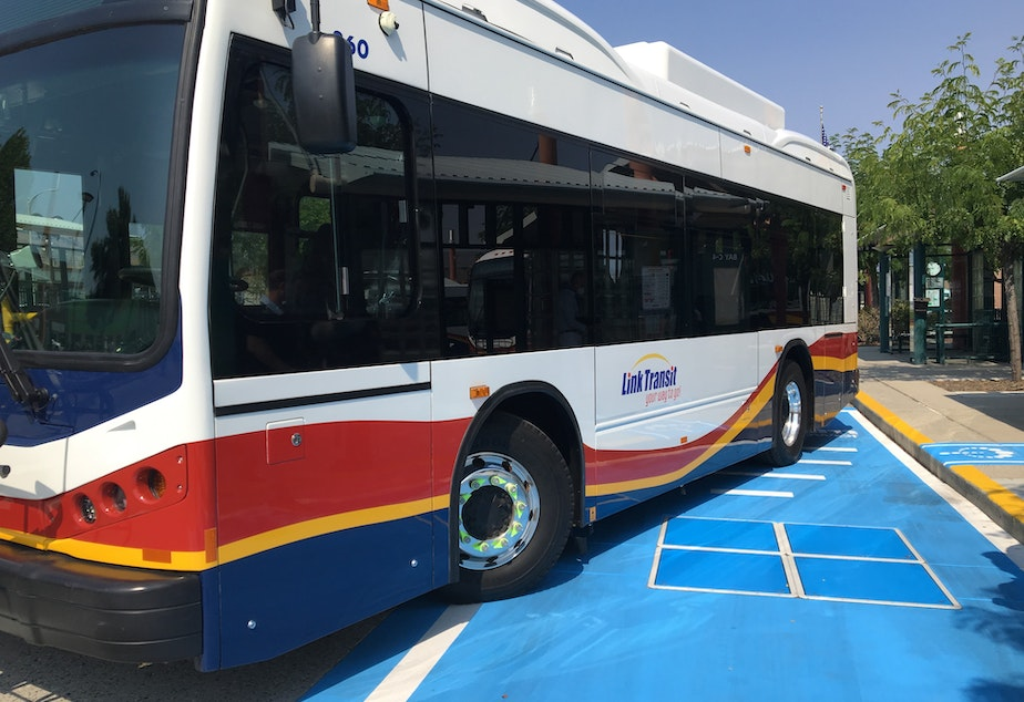 caption: A Link Transit electric bus and a wireless charging station at a bus stop in Wenatchee, Washington