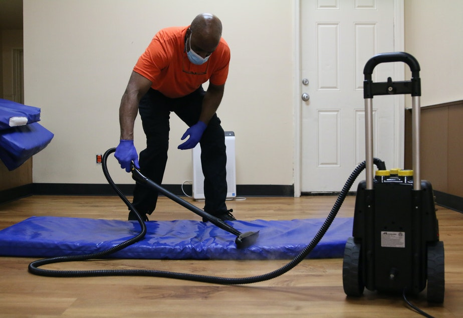 caption: Tony Zachary demonstrates the steam cleaner at the Bread of Life Mission. It's part of their Covid safety protocols.