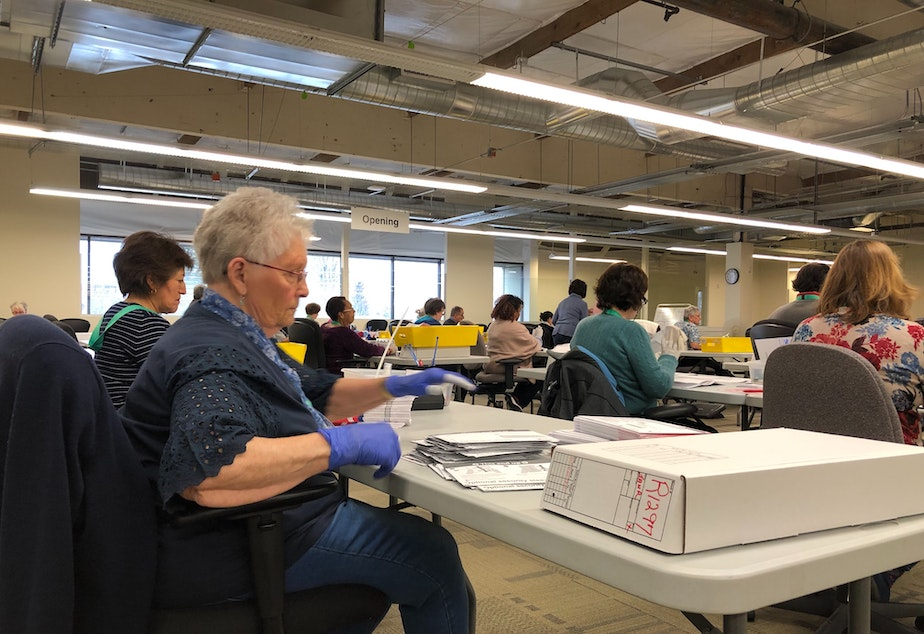 caption: King County Elections has hired up to 150 temporary staff to process ballots. Jane Reese, left, says they're taking precautions to prevent virus transmission.