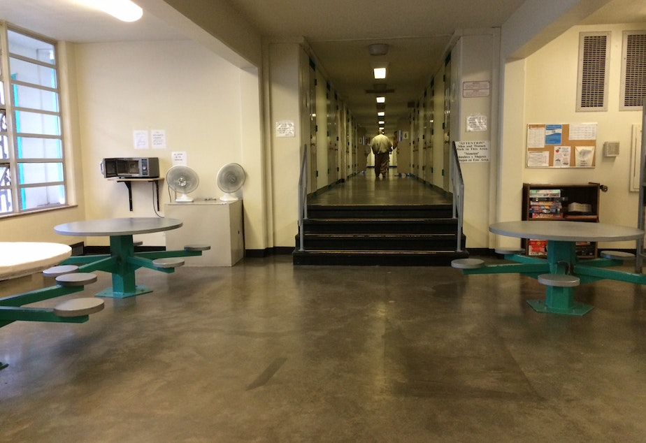 caption: An inmate walks along the housing tier in the DOC's Skill Building Unit.