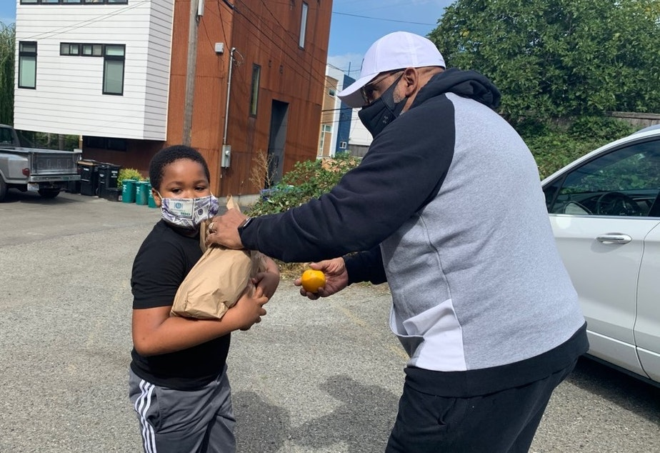 caption: Gerald  Donaldson, a family support worker at Leschi Elementary in Seattle, helps deliver school lunches during the Covid-19 pandemic.