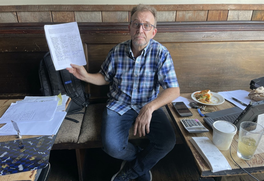 caption: Christopher Forczyk owns Smith, a bar on 15th Avenue. He holds up a petition of business owners he says oppose the proposed Business Improvement Area