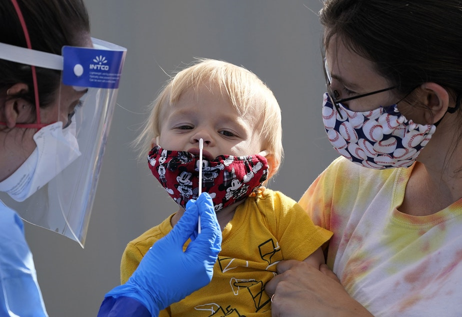 caption: One-year-old Quentin Brown, is held by his mother, Heather Brown, as he eyes a swab while being tested for COVID-19 at a new walk-up testing site at Chief Sealth High School, Friday, Aug. 28, 2020, in Seattle. The child's daycare facility requires testing for the virus. The coronavirus testing site is the fourth now open by the city and is free.