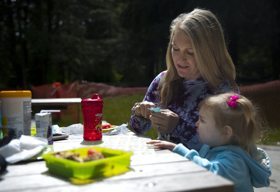 caption: Julie Wright and her daughter Stella, age 2, eat lunch at the Discovery Park play area on Wednesday.