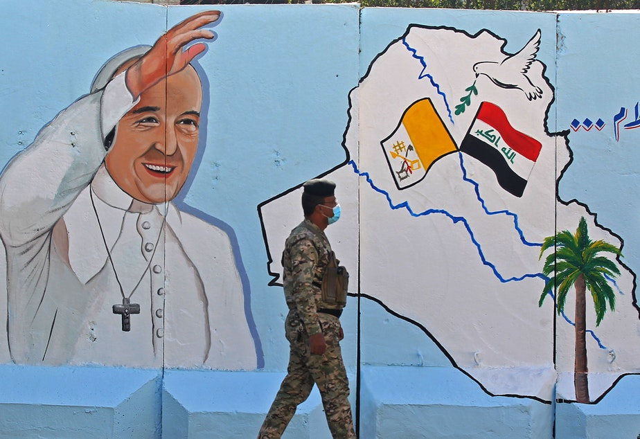 caption: An Iraqi policeman walks by a mural depicting Pope Francis on the outer walls of Our Lady of Salvation Church in Baghdad on Monday. Pope Francis' visit from March 5 to 8 will include trips to Baghdad, the city of Mosul and a meeting with the country's top Shiite cleric Grand Ayatollah Ali al-Sistani.