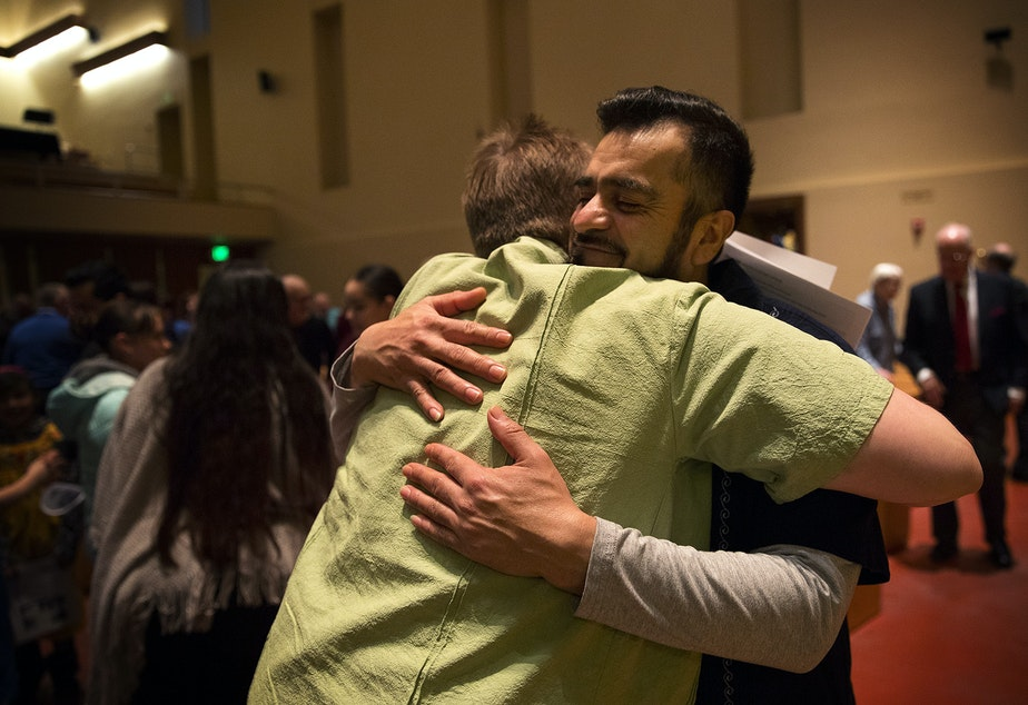 caption: FILE PHOTO: Jose Robles, right, hugs Pastor Kari Lipke on Sunday, December 16, 2018, after the Las Posadas Pageant at Gethsemane Lutheran Church in Seattle.