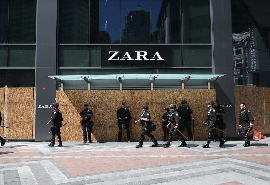 caption: Police officers walk in front of Zara's ahead of a peaceful protest march on Monday, June 1, 2020, beginning at Westlake Park in Seattle.
