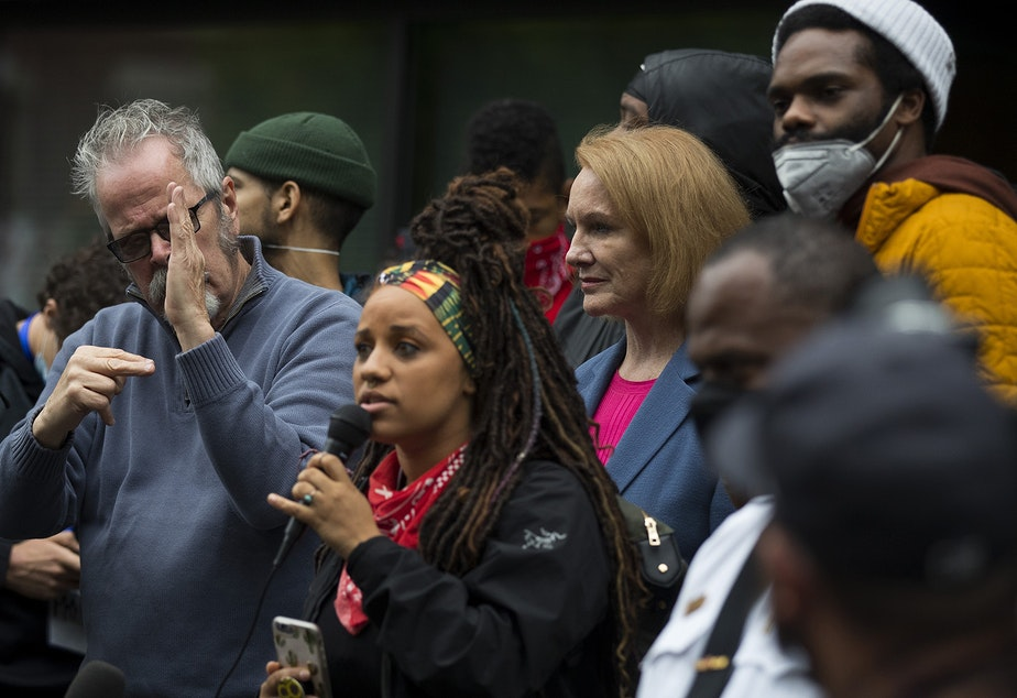 caption: Seattle Mayor Jenny Durkan stands between organizers Rashyla Levitt and David Lewis, right, on Tuesday, June 2, 2020, outside of the Emergency Operations Center in Seattle. Mayor Durkan promised a crowd of thousands that she would meet with organizers the following day.