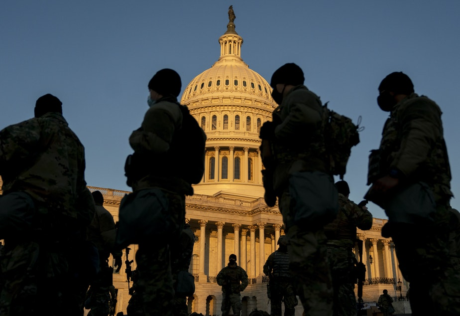 caption: Members of the National Guard gather outside the U.S. Capitol — part of a massive boost to security after the riot last Wednesday, and leading up to Inauguration Day.