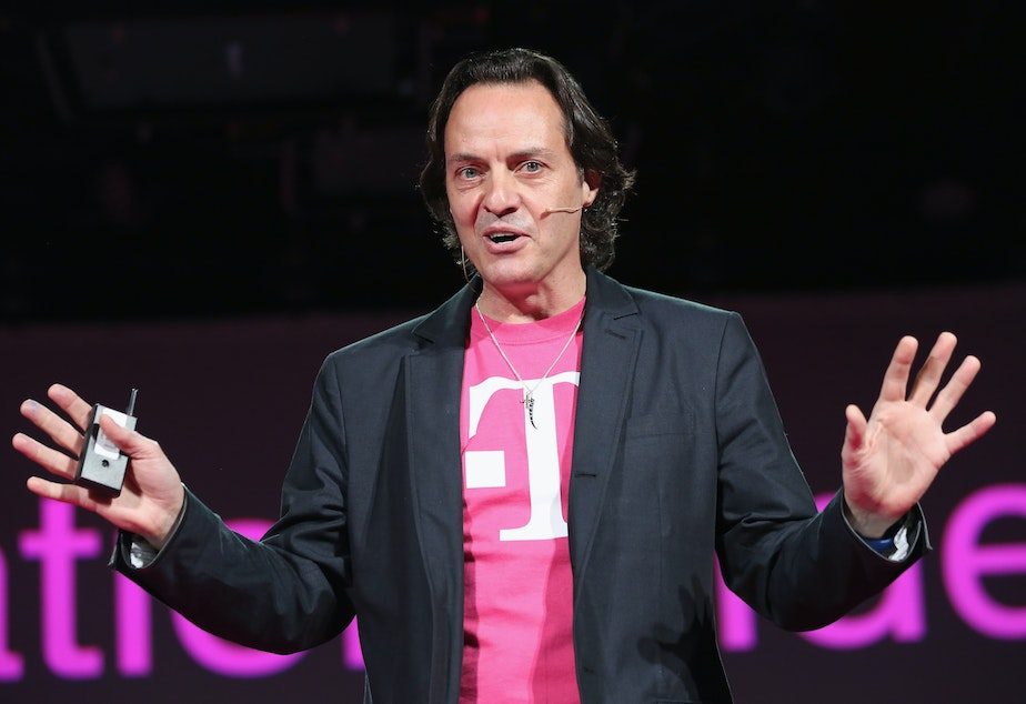 caption: John Legere, CEO and president of T-Mobile USA, sports one of his distinctive magenta T-shirts. Its parent, Deutsche Telekom, is telling a small insurance company not to use the color.