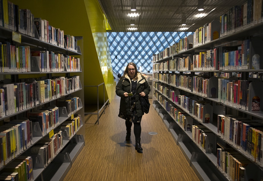 caption: Kara Peters walks through the Seattle Public Central Library to her desk before starting her shift on Wednesday, January 22, 2020, in Seattle.