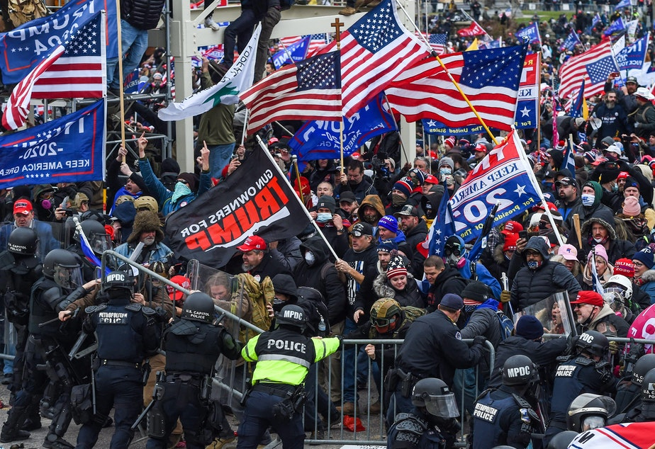 caption: Police and security forces attempt to hold back a mob of pro-Trump extremists as they storm the U.S. Capitol in Washington on Wednesday.